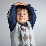 O retrato do estúdio de um rapaz pequeno bonito, uma criança jogou suas mãos atrás de sua cabeça imagens de stock