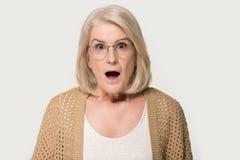 O retrato do estúdio do Headshot envelheceu a mulher chocada surpreendida isolada no cinza fotografia de stock
