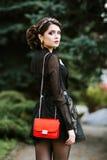 O retrato do estilo de vida da mulher à moda nova vai na cidade com um saco na moda vermelho No saco de embreagem do ombro da men Fotos de Stock