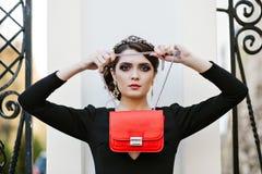O retrato do estilo de vida da mulher à moda nova vai na cidade com um saco na moda vermelho No saco de embreagem do ombro da men Imagem de Stock
