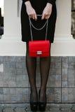 O retrato do estilo de vida da mulher à moda nova vai na cidade com um saco na moda vermelho No saco de embreagem do ombro da men Imagens de Stock