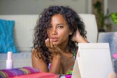 O retrato do estilo de vida da mulher latino-americano preta exótica lindo e feliz nova que olha a câmera sedutor após a aplicaçã fotos de stock
