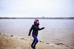 O retrato do estilo de vida da mulher magro caucasiano nova corre ao longo do outono da praia Imagens de Stock