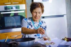 o retrato do estilo de vida do japonês asiático feliz e doce superior aposentou-se a mulher que cozinha em casa a cozinha apenas  fotos de stock royalty free
