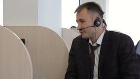 O retrato do gerente de banco que fala ao cliente que usa seus fones de ouvido vídeos de arquivo