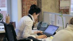 O retrato do gerente fêmea novo que consulta o cliente por um email em seu portátil filme