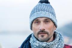 O retrato do homem branco no inverno fez malha o chapéu e o lenço Feche acima do indivíduo farpado no chapéu e no lenço azul-bran fotografia de stock royalty free