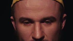 O retrato do homem cansado novo com a barba no tampão amarelo abaixa os olhos e é vesgo filme