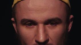 O retrato do homem caucasiano novo com a barba no tampão amarelo abaixa os olhos cansados video estoque