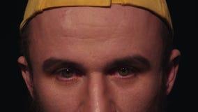 O retrato do homem caucasiano novo com a barba no tampão amarelo olha na câmera filme