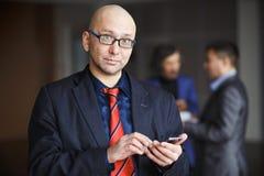 O retrato do homem com o homem de negócios calvo dos vidros que usa o telefone à disposição, o terno listrado vestido e o laço ve foto de stock royalty free