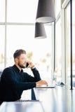 O retrato do homem de negócio farpado novo fala no telefone que trabalha no portátil no escritório moderno fotos de stock
