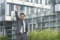 O retrato do homem de negócios alegre com braço aumentou o prédio de escritórios exterior ereto imagem de stock royalty free