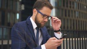 O retrato do homem de negócios bem sucedido está usando o smartphone no fundo da construção da cidade video estoque