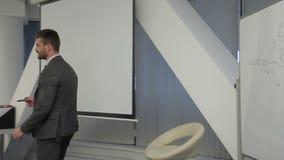 O retrato do homem de negócios bem sucedido que está apresentando o progect digital do investition da moeda na conferência video estoque