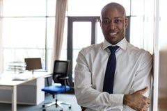O retrato do homem de negócios novo de sorriso com braços cruzou a inclinação no armário no escritório Fotografia de Stock Royalty Free