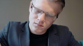 O retrato do homem de negócios novo está trabalhando no projeto no escritório moderno filme