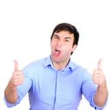 O retrato do homem de negócios novo feliz que guarda os polegares isolou acima o Fotos de Stock Royalty Free