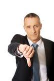 O retrato do homem de negócios que mostra o polegar assina para baixo Imagens de Stock