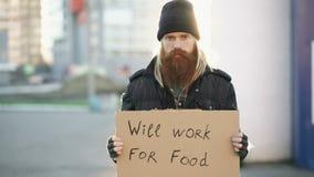 O retrato do homem desabrigado novo com o cartão que olha a câmera e quer trabalhar para o alimento que olha a câmera na rua filme