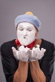 O retrato do homem engraçado mimica com chapéu cinzento e Fotografia de Stock