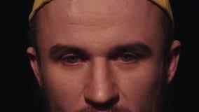 O retrato do homem esgotado jovens com a barba no tampão amarelo olha na câmera filme
