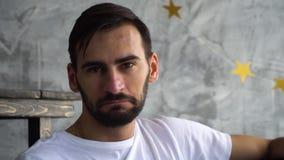 O retrato do homem farpado no olhar branco da camisa de t in camera e inclina-se seus símbolos principais que você é direito filme