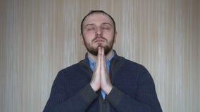 O retrato do homem farpado novo esperançoso mantém as mãos junto em rezar o gesto filme