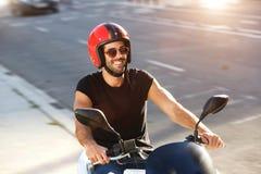 O retrato do homem feliz com capacete e os óculos de sol na motocicleta montam imagens de stock royalty free