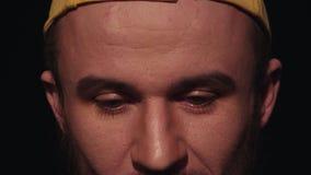 O retrato do homem incerto novo com a barba no tampão amarelo pisca repetidamente video estoque
