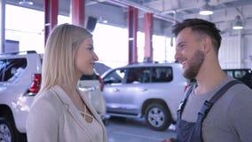 O retrato do homem do mecânico e da mulher de sorriso do consumidor comunica-se sobre reparações de automóveis video estoque