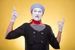 O retrato do homem mimica isolado no amarelo Fotos de Stock Royalty Free