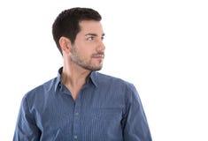 O retrato do homem novo considerável que olha lateralmente na camisa azul é Fotos de Stock Royalty Free