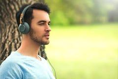 O retrato do homem novo de sonho bonito com fones de ouvido, escuta música no fundo da árvore Fotografia de Stock
