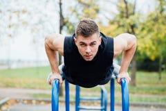 O retrato do homem novo muscular focalizado no exercício preto veste fazer mergulhos em barras paralelas imagens de stock royalty free