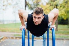 O retrato do homem novo muscular focalizado no exercício preto veste fazer mergulhos em barras paralelas fotos de stock