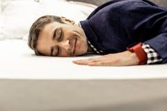 O retrato do homem sereno com olhos fechou o encontro na cama fotografia de stock