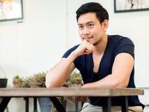 O retrato do homem do sorriso senta-se e relaxa-se no café do café fotografia de stock