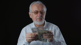 O retrato do homem superior em uma camisa branca conta notas de dólar video estoque