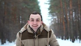 O retrato do homem surpreendido em um revestimento está mostrando uau a emoção na câmera O homem est? na floresta do inverno video estoque