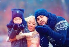 O retrato do inverno de sopro da família feliz neva fora fotografia de stock royalty free