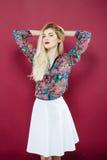 O retrato do louro sensual na camisa e na saia coloridas do branco está olhando a câmera no fundo cor-de-rosa Menina surpreendent Foto de Stock Royalty Free