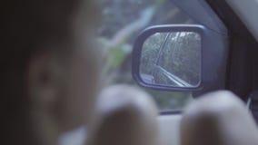 O retrato do marrom novo eyed a fêmea com os joelhos desencapados que sentam-se em carro movente video estoque