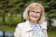 O retrato do meio bonito envelheceu a mulher no parque do verão fotografia de stock