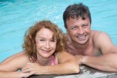 O retrato do meio feliz envelheceu os pares que relaxam na borda da piscina imagem de stock