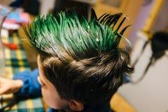 o retrato do menino da criança de 9 anos em casa com crista do verde coloriu h foto de stock royalty free