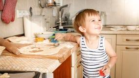 O retrato do menino de sorriso pequeno que cozinha sobre kithcen em casa Cozimento da criança e massa da fatura fotos de stock royalty free