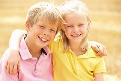O retrato do menino e da menina no verão colheu o campo Fotografia de Stock