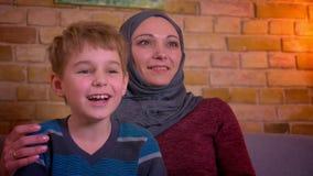 O retrato do menino pequeno e de sua mãe muçulmana no hijab estourou para fora rindo a comédia alegremente de observação na tevê  video estoque