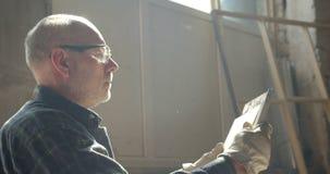 O retrato do mestre superior da carpintaria verifica a qualidade e o tamanho de uma placa de madeira na fabricação video estoque